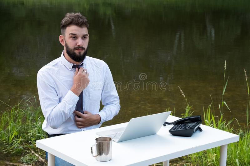 Morning businessman in a white shirt. A guy with a beard sits at a table with a laptop, a mug of coffee against of the river and stock photo