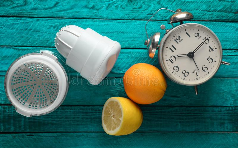 Morning fresh juice from lemon and orange. Handmade juicer, alarm clock, citrus fruit on a blue wooden background. Top view.  royalty free stock image