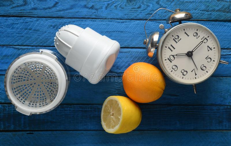 Morning fresh juice from lemon and orange. Handmade juicer, alarm clock, citrus fruit on a blue wooden background. Top view.  stock images