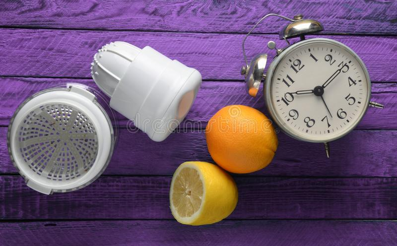Morning fresh juice from lemon and orange. Handmade juicer, alarm clock, citrus fruit on a violet wooden background. Top view.  stock photography