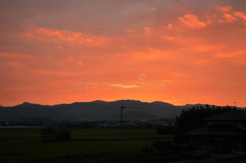 Morning glow. Crossing birds flocking in the sky dyed red in the morning glow and the sound of the water flowing in the Chikugo River can be heard. Today is a stock photos