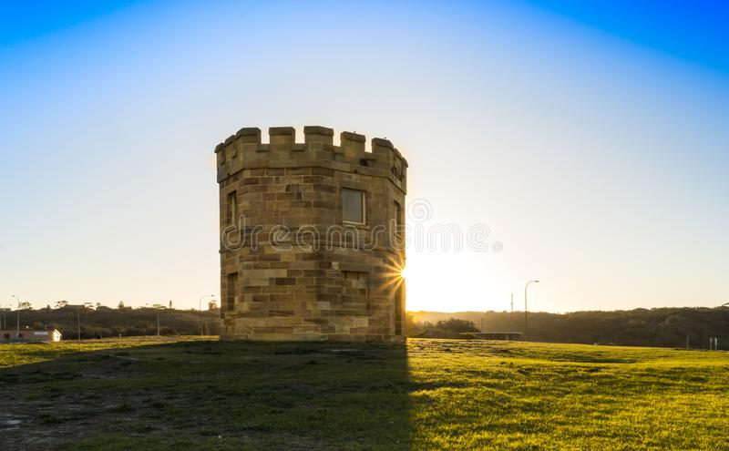 Macquarie Watch Tower at Sunrise. Morning glow of the sun lighting up behind the historic Macquarie Watch Tower in Sydney, Australia royalty free stock images