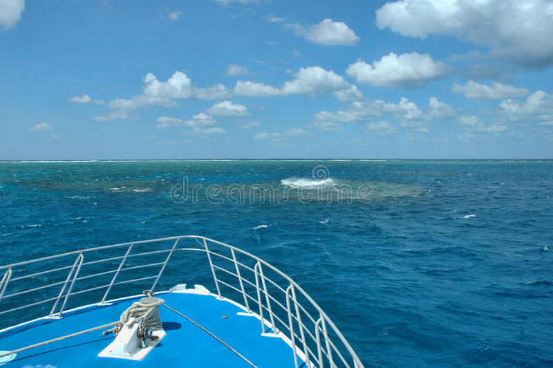 Morning on the Great Barrier Reef. Waves break on the reef under blue sky on a liveaboard on the Great Barrier Reef, Australia stock photo