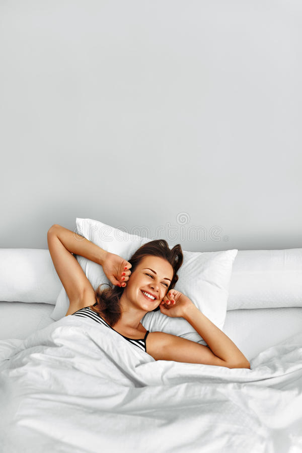 Morning. Healthy Woman After Wake Up Relaxing In Bed. Wellness. Healthy Lifestyle. Beautiful Happy Smiling Woman Lying Fully Rested After Wake Up On White royalty free stock photos
