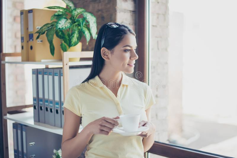 Morning is here! Close up side portrait of dreamy cute latin mulatto lady drinking coffee. She is relaxed and looking in the wind stock images