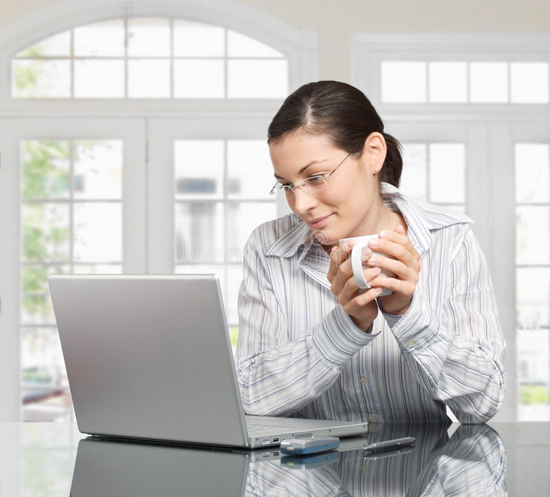 Morning at home. Young woman looks at her laptop computer and drinks her coffe. It is early morning in a light and clean home interior dominated by white and stock image