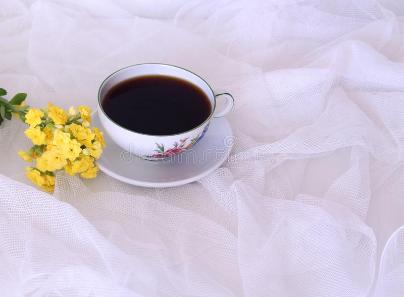 Morning hot coffe in mug and little yellow flower kalanchoe. on white satin background. Copy space. Closeup, top view. Seasonal, m stock photography