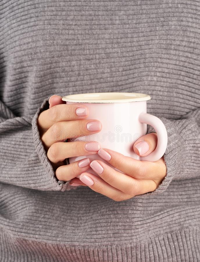Morning hot coffee at work on a cold autumn morning, hands holding a mug with a drink, gray sweater, pink manicure, close up,. Morning hot coffee at work in stock image
