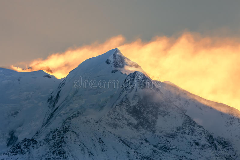 Morning Hours on Mont Blanc. Backlit image at the sunrise on Mont Blanc - the highest mountain peak in Europe. In the first plan you can see L'aiguille de royalty free stock photography