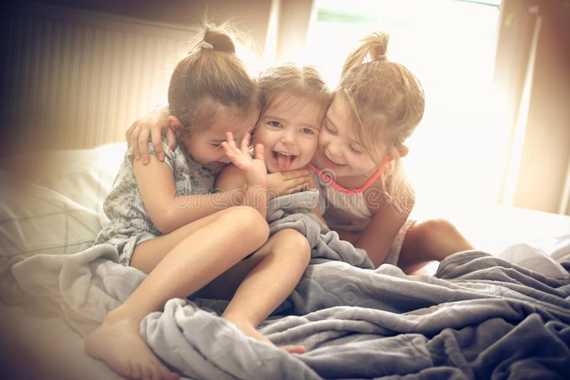 Morning hug. Kids on bed. Three little girls plying in bed. Space for copy royalty free stock photos