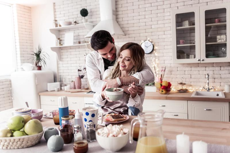 Pretty long-haired young woman in a white shirt and her husband standing in the kitchen. Morning hugs. Pretty long-haired young women wearing a white shirt and royalty free stock image