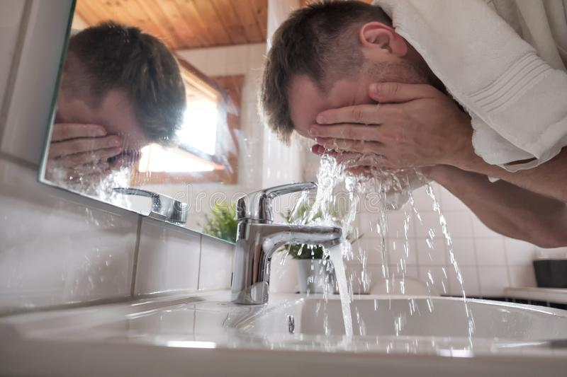 Caucasian man washing face in a wash basin in white washroom stock photo