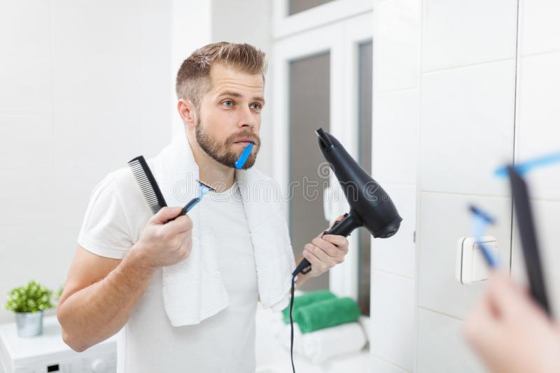Morning hygiene, Man in the bathroom and his morning routine. Morning hygiene, Handsome man in the bathroom and his morning routine stock photography
