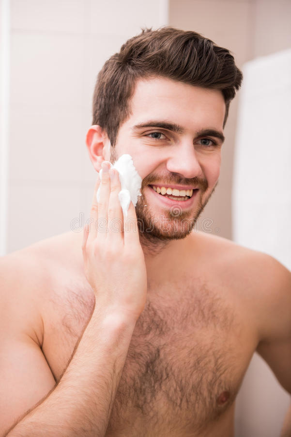 Morning hygiene. Portrait of a handsome young man is applying shaving cream to his face stock photo