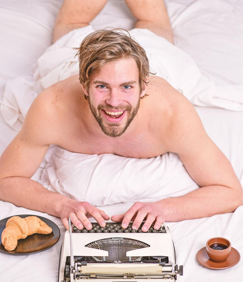 Morning inspiration. Erotic literature. Daily routine of writer. Writer handsome author used old fashioned manual. Typewriter. Man writer lay bed with breakfast royalty free stock images