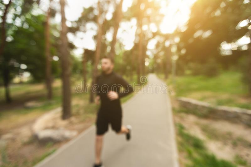 Morning jogging background. Blurred shot of man running in city park stock photography