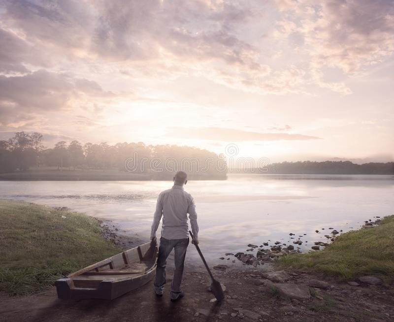 Morning at the lake. A man prepares to go on a lake at sunrise stock photos