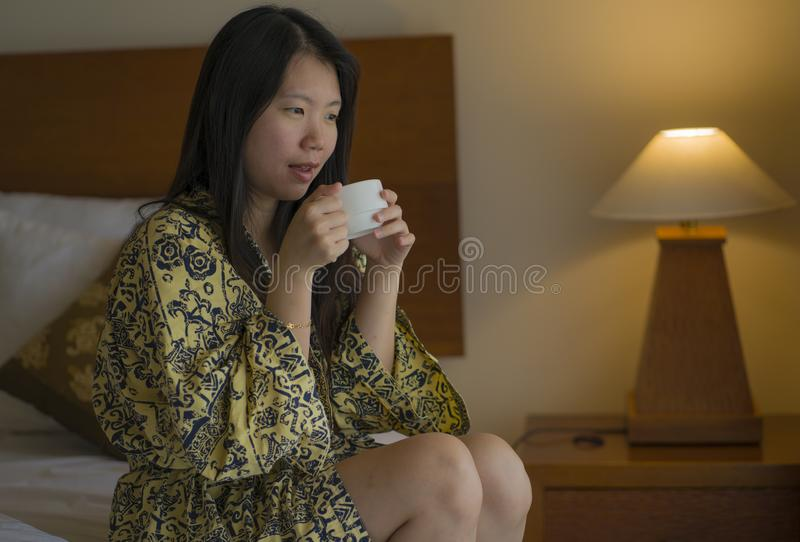 Morning lifestyle portrait of young beautiful and natural Asian Chinese woman drinking coffee in bed after wake up smiling happy royalty free stock image