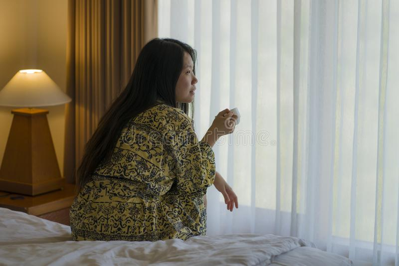 Morning lifestyle portrait of young beautiful and natural Asian Chinese woman drinking coffee in bed after wake up smiling happy royalty free stock photos