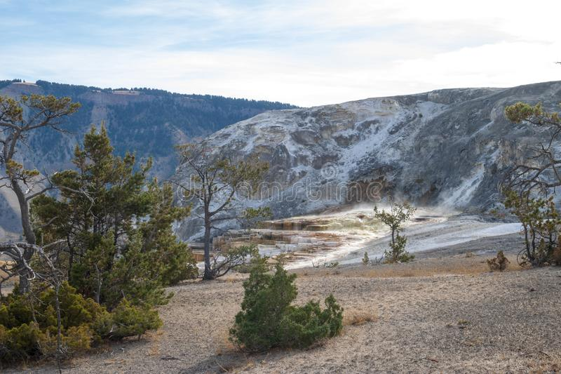 Morning light begins to illuminate the top of Mammoth Hot Springs stock image