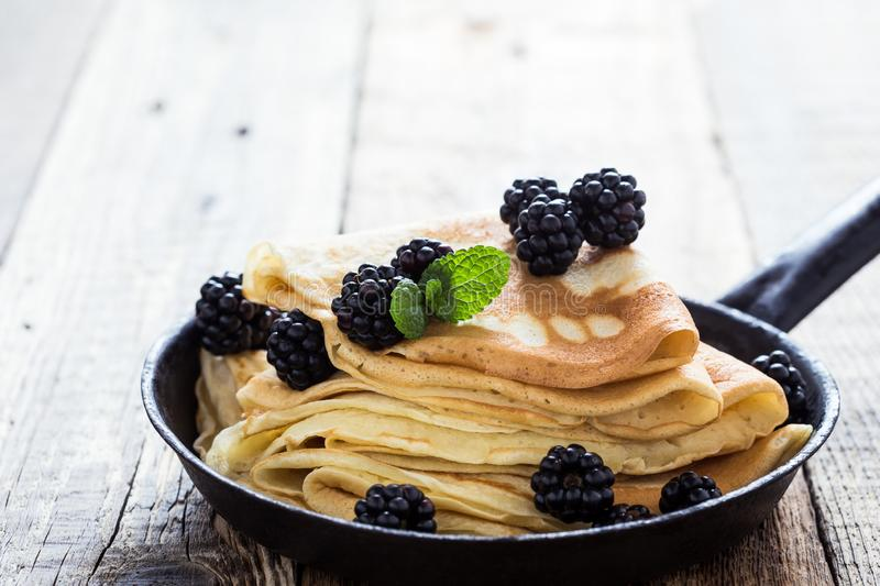 Morning meal, homemade crepes, fresh summer blackberries. Healthy breakfast or brunch, favorite morning meal. Homemade crepes, fresh summer blackberry berries in stock images