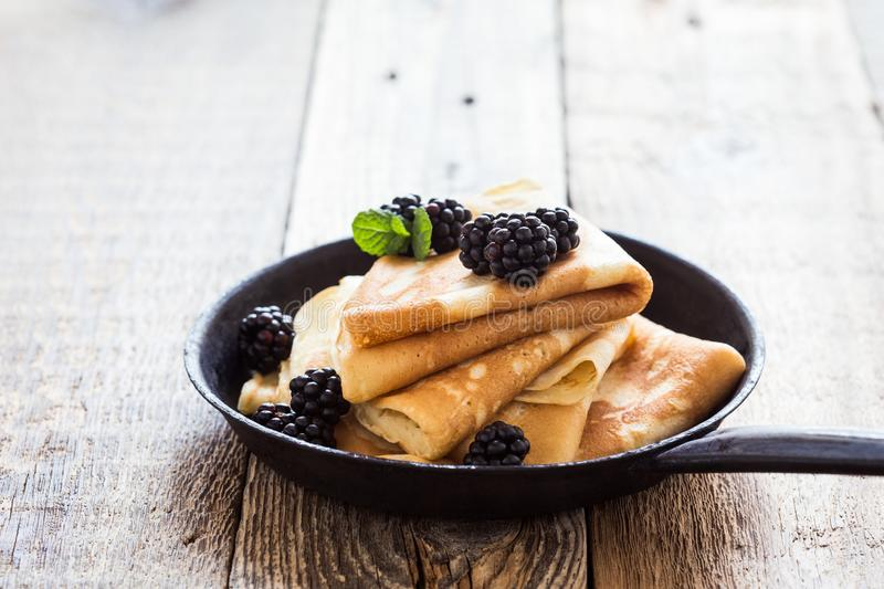 Morning meal, homemade crepes, fresh summer blackberries. Healthy breakfast or brunch, favorite morning meal. Homemade crepes, fresh summer blackberry berries in royalty free stock photo