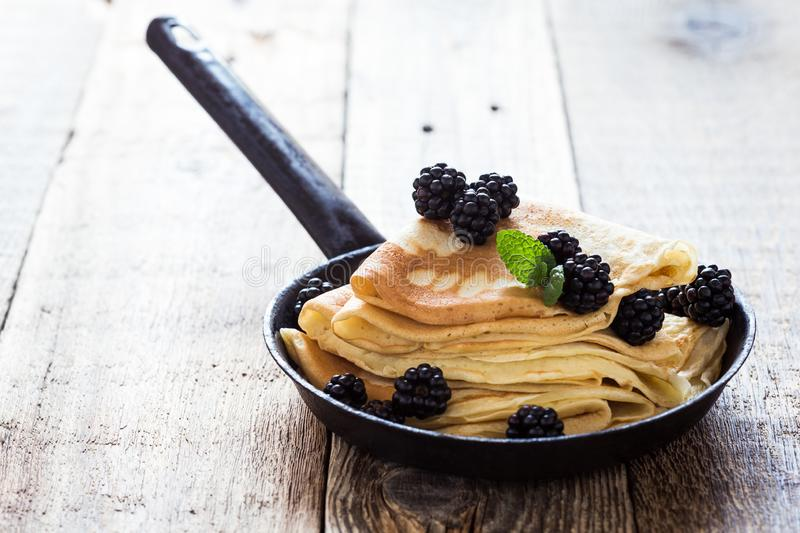 Morning meal, homemade crepes, fresh summer blackberries. Healthy breakfast or brunch, favorite morning meal. Homemade crepes, fresh summer blackberry berries in stock photo