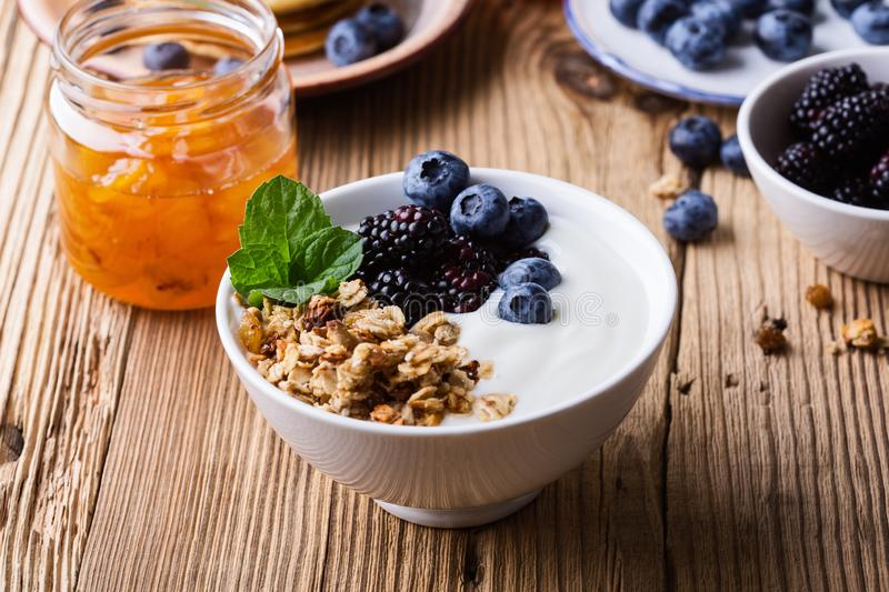 Morning meal, homemade granola with yogurt, fresh summer berries, fruits royalty free stock photos