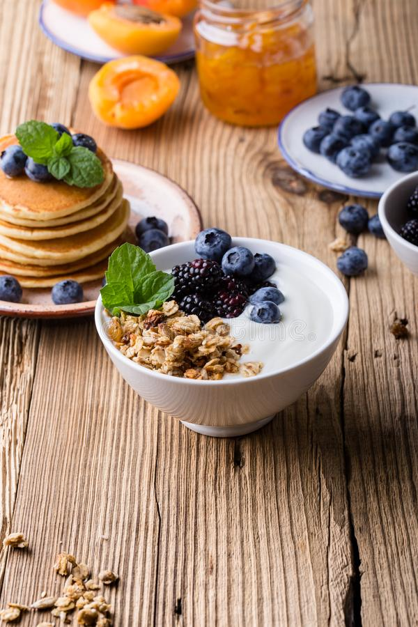 Morning meal, homemade granola with yogurt, fresh summer berries, fruits royalty free stock photo