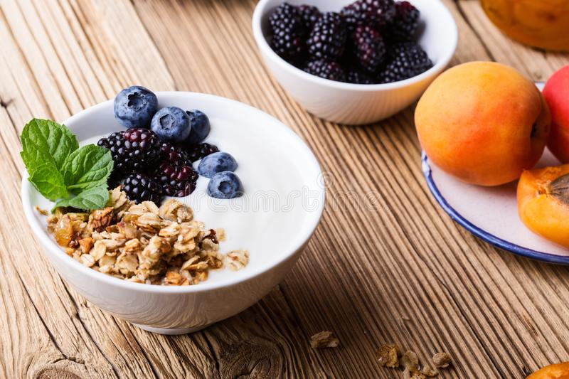 Morning meal, homemade granola with yogurt, fresh summer berries, fruits stock image