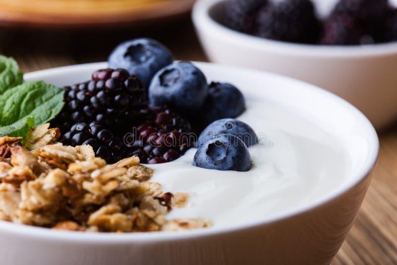 Morning meal, homemade granola with yogurt, fresh summer berries, fruits stock photo