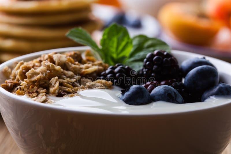 Morning meal, homemade granola with yogurt, fresh summer berries, fruits royalty free stock photos