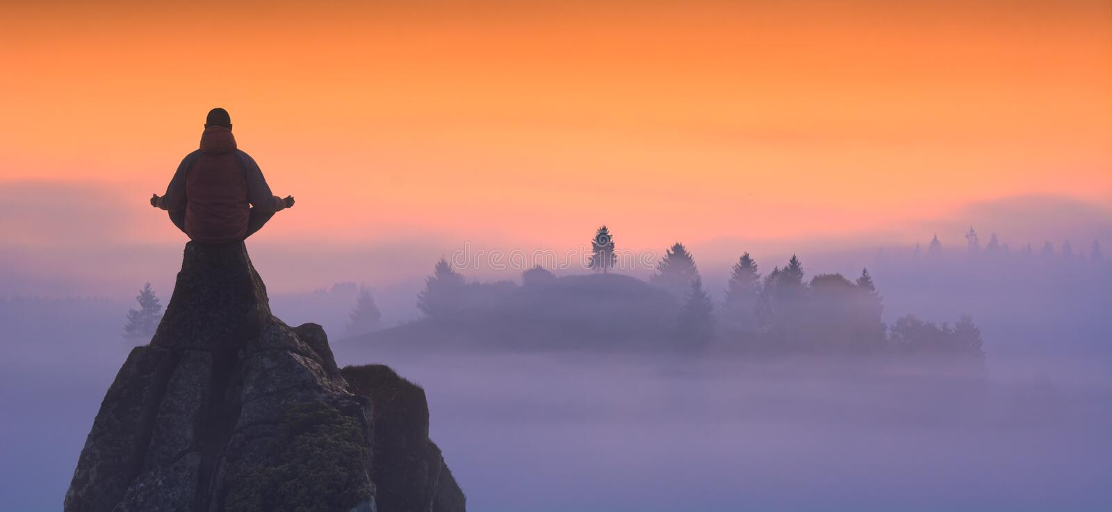 Morning meditation. Silhouette of human who meditating in sitting yoga position on the top of mountain against misty valley. Zen, meditation, peace stock images