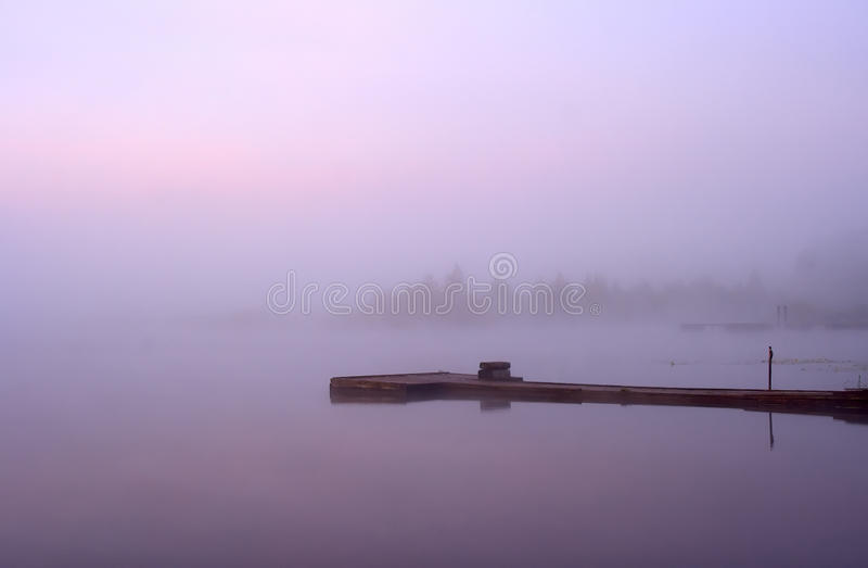 Lake Seliger: morning mist moorage. Morning nature scene (landscape): fog (mist) reflected in the water surface along with pink and blue sky, trees and moorage ( stock photos