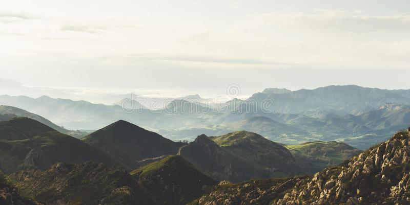 Morning mist in the mountain peaks on natural landscape. Green valley on background foggy dramatic sky, mountain tops. Panorama. Horizon perspective view of royalty free stock photography