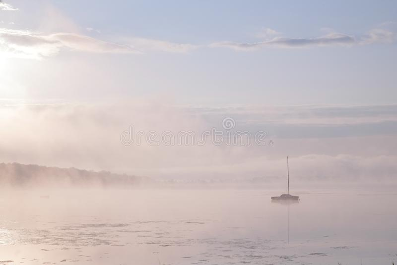 Morning mist over lake with sailboat stock photo