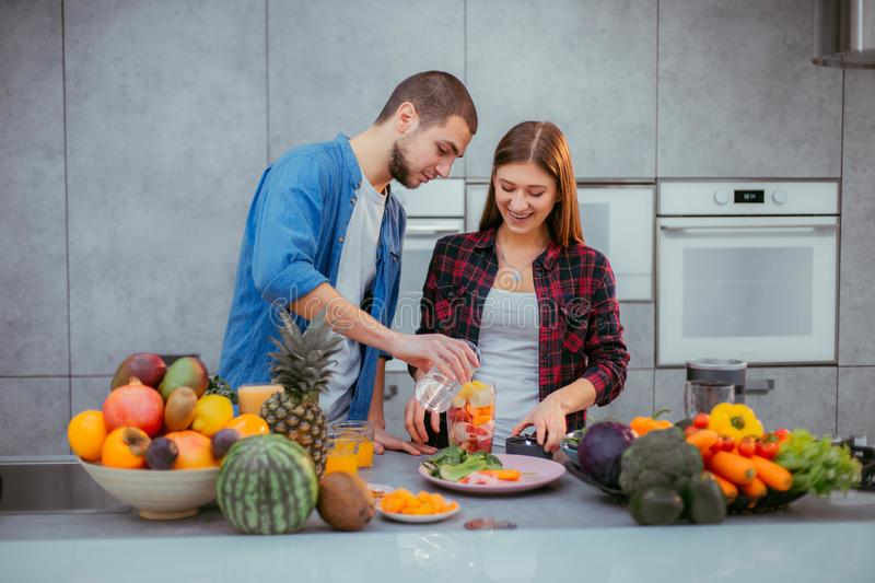 In the morning a modern kitchen charismatic couple making a fresh smoothie for the breakfast stock images