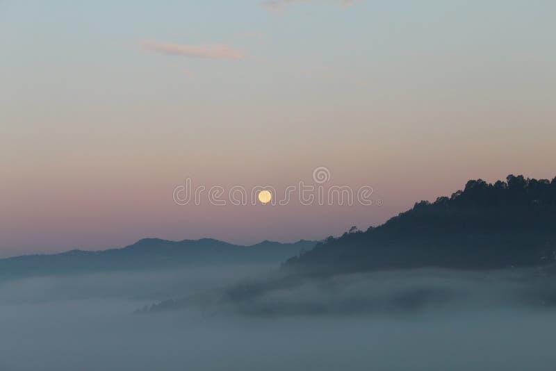 Morning moon boven de heuvels in de rode hemel met Fog royalty-vrije stock foto