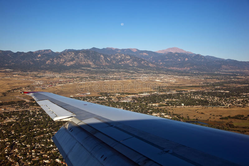 Morning Moon over Colorado Springs, Colorado. Flying into the Colorado Springs Airport with a morning moon and Pike's Peak royalty free stock images