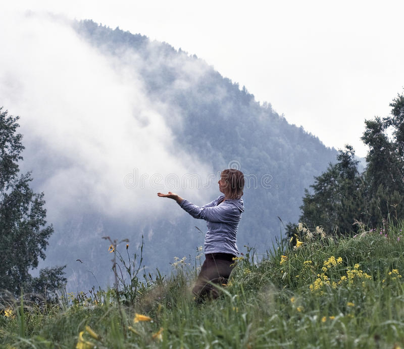 In the morning, on a mountain woman meditates. Early foggy morning, on a mountain woman meditates royalty free stock photos