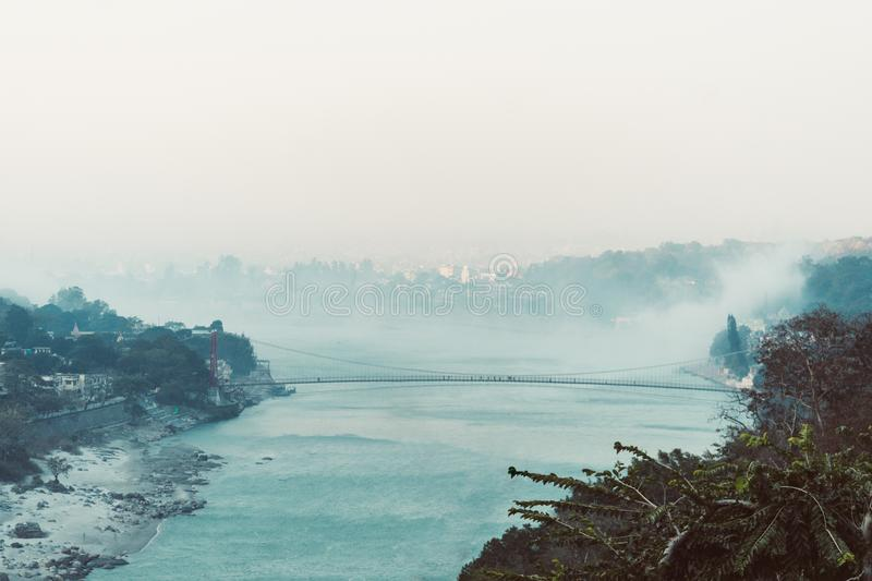 Morning in the mountains. The Ganges River in the foothills of the Himalayas. India. view of Lakshman Jhula bridge early morning. Smoke on the water royalty free stock photography