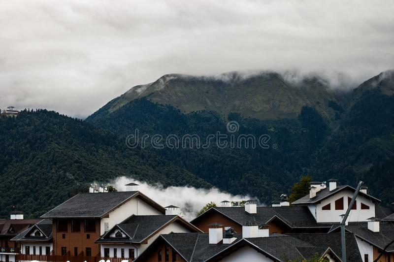 Morning in the mountains after the rain. White clouds.black roof royalty free stock photography