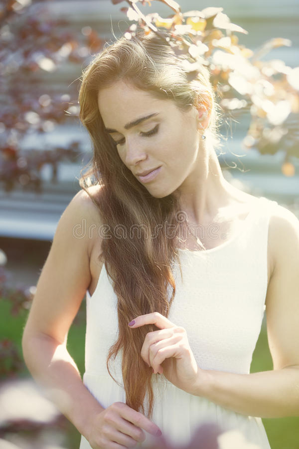 Morning in the park. Young attractive woman with the long hair enjoying morning in the park stock photography