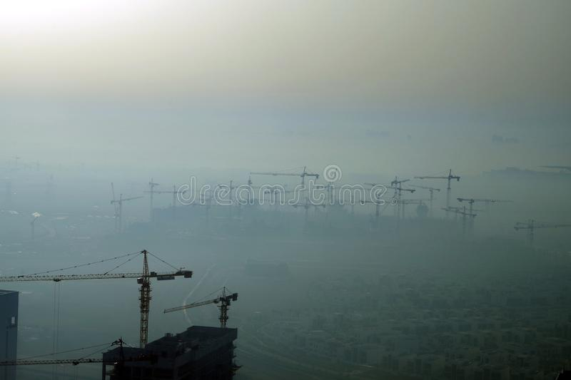 Morning picture of a work construction site with in background a large group of cranes emerging from the fog. Morning picture of a work construction site with stock photo