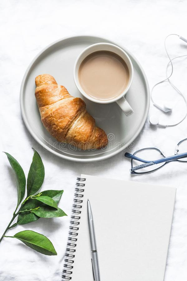 Morning plan. Coffee, croissant and  clean empty notebook on a light background, top view. Flat lay, copy space royalty free stock photos