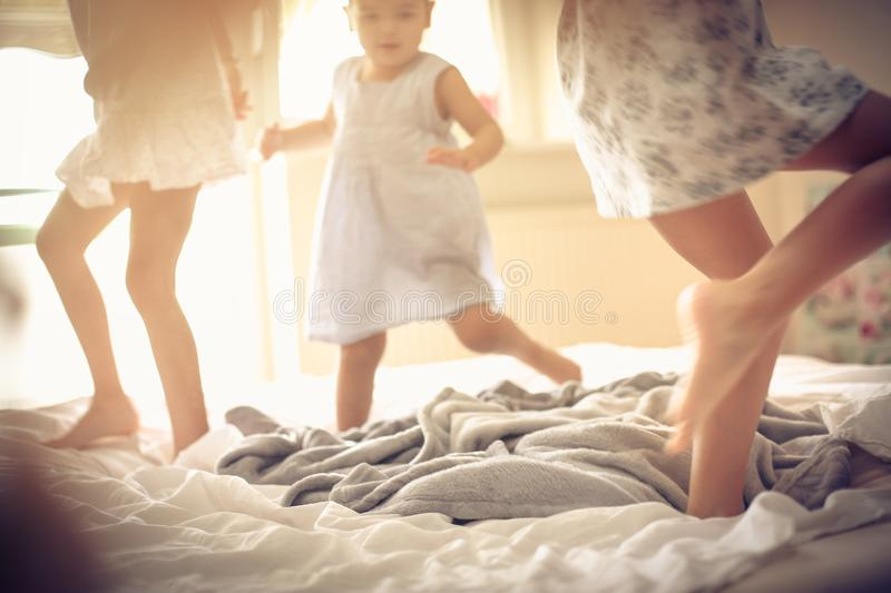 Morning play. Kids on bed. Three little girls dancing in bed. Space for copy royalty free stock photos