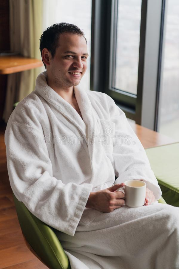 Morning portrait of handsome young man with cup of coffee royalty free stock image