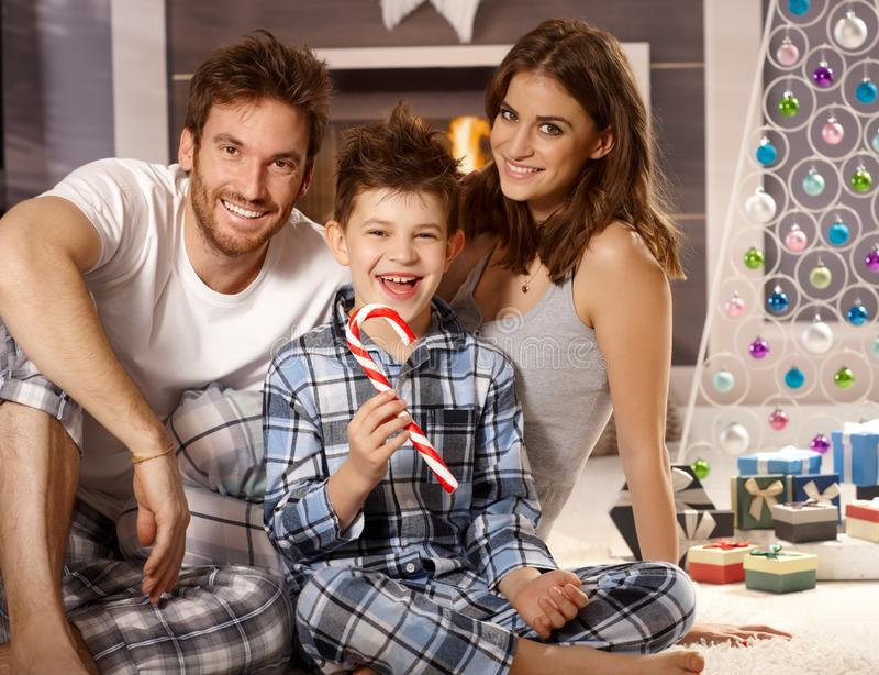 Morning portrait of happy young family. Portrait of happy young family at christmas morning, little boy having lollipop royalty free stock photos