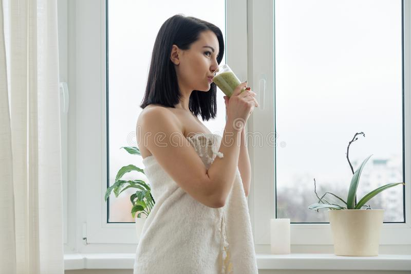 Morning portrait of young beautiful woman in bath towel at home near the window drinking freshly blended green kiwi fruit smoothie royalty free stock image