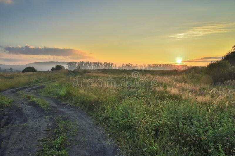 Morning, rising sun over the field and dirt road, with trees and country buildings royalty free stock photography